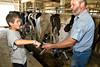 """Ira sticks his finger in the """"sucker"""" end of the milking machine.<br /> <br /> With my good friend Doug Hermsen on Doug's dairy farm in Colesburg, Iowa. We spent the day and night with Doug, with Ira getting to see where milk REALLY comes from. <br /> <br /> I spent the better part of three years with Doug in the Marines, including one overseas deployment.<br /> <br /> Thanks, Doug, for having us up. I don't think either of us will ever forget this trip!!"""