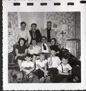 Probably Thanksgiving or Christmas Eve; definitely Morgan Court, Portland, Maine, about 1951. I can tell the location by recollecting that old wallpaper.  How did Dad and Ma ever get them all over there to that old place?    See the silver radiator in the image's mid-right?  That is how they heated back then.  It is filled with hot water that circulates down into the furnace in the cellar and back through to all the radiators in each room.  That system was heated with COAL.  Bruce and I can remember the coal being delivered.  The chute went through an open cellar window and was piled in a corner in a bin.  Although I did not see it, Dad had to go down there and shovel the coal into the coal furnace.  I have one other memory of that cellar.  One day I remember seeing a huge rate down there.    It is funny how things change.  All that furniture is since gone to the dump many years ago.  But I would like to have a few pieces back right now, just for nostalgia.  I remember seeing Dad lying on that couch with such severe pain that it was the only time in my life I saw him screaming.  He had a severe ear ache.  Oh, and one other memory there:  Ma had one of those old clothes washers that had a wooden roller on the top.  You would take each soaked piece of clothing and roll it through the wooden rollers to wring out the excess water, before hanging the clothes out on the line.      Left to right, front row to back row:  Ricky (our Belgium Shepard that I still so deeply miss), Bruce McClean King (my Brother)....I did not know they had flannel -lined jeans back then, Carol King (my Aunt) with her little watch and necklace, David George King (my Uncle), me (Robert Lee King Jr.) at about 3 years of age (I turned 65 last week), with the strap hanging off there and the dirty face.  How did Ma ever keep me clean?  I cannot have the t-shirt back but can I hope technology catches up to the point that in the future someone can discern the front of it.  Ricky is not as old as he look