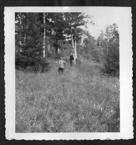 "David George King (facing) and Bruce McClean King in a meadow (circa 1954), probably at the site of the ""old camp"", Kingfield Township, Maine."