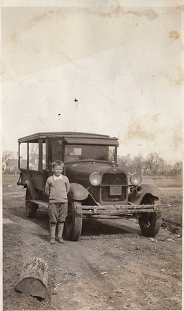 """Robert Lee King Sr. (Dad, 1926-2008)) at 8 years of age in 1934, at where I believe to be the beginnings of Rosedale Street, Portland, Maine.  The folks at Antique Automobile Club of America's forum (AACA.com) identified the truck as a 1929 Ford Model A with an all-wood cargo box.  Some were a combination of wood and steel.   I verified they were correct when I """"google imaged"""" that make, model and year.  Thanks to AACA.com and Google Images.  Yes, it is curious why Dad is holding his hands behind his back.  Kids are not disciplined to do it today are they?  Nope.  All I know is this:  Grammy (my late Grandmother and Dad's Mother) told me that when Dad was young she imprinted onto him that """"he was gonna be a gentleman if it killed him"""".  And so, she named him after Robert E. Lee, that well-known gentleman and Southern Confederate General"""