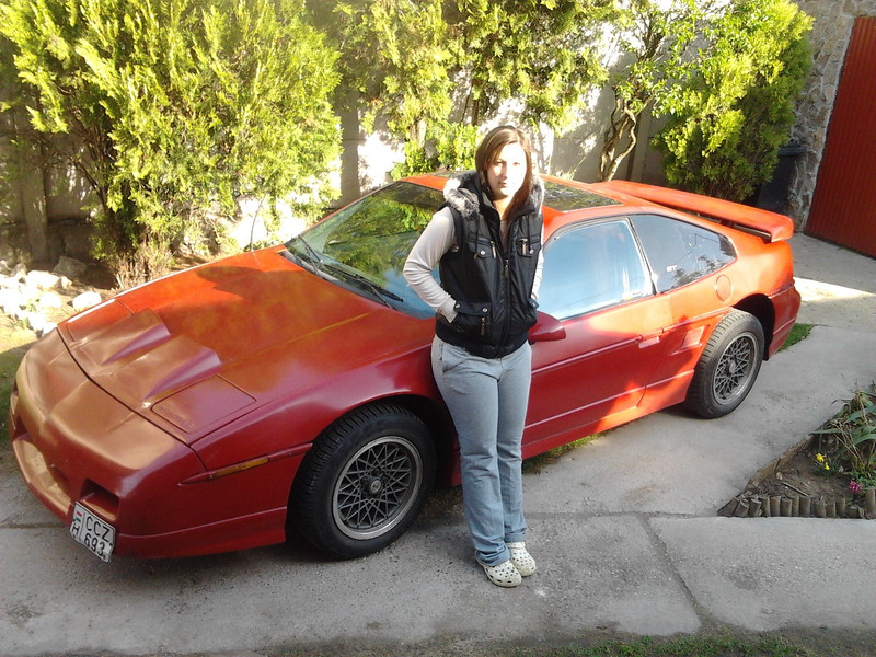 Brigitta standing by her American car.  My guess is a souped up 1985 -1988 Pontiac Fiero