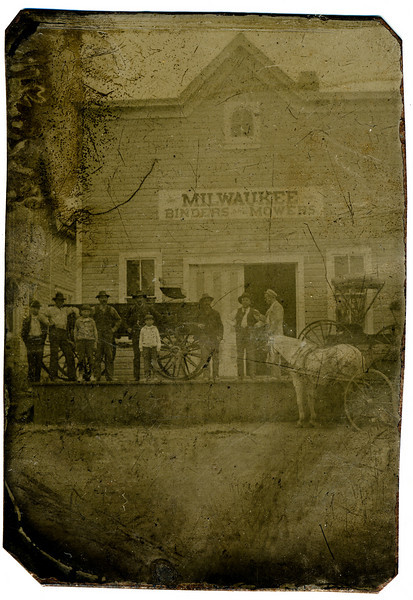 """Tintype. Unknown date, location, and people. This tintype, I am told, belonged to George or Annie Esch and then came into the possession of Levi and Martha. The original tintype image is quite faded and scratched, but the scan and photo imaging software make it more viewable. If you place your cursor over the photo, a menu will appear that allows you to see larger versions of the image. The """"original"""" size is very large and gives you the best view of the faces, but the file takes a little time to load. Some of the faces could be Esches?  I wish I knew.  I believe that the Milwaukee Binders and Harvesters sign refers to a company that manufactured these farm implements.  That company was bought in 1902, along with Deering and McCormick, to form part of International Harvester. Any ideas on who these people might be, or where this is?"""