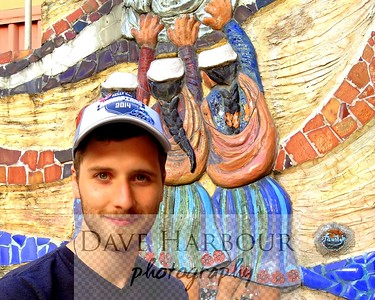 Cuenca, Billy Harbour in craft market area posing before clay-mosaic mural.