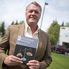 UAA professor of finance, John Nofsinger poses with his book: The Psychology of Investing.