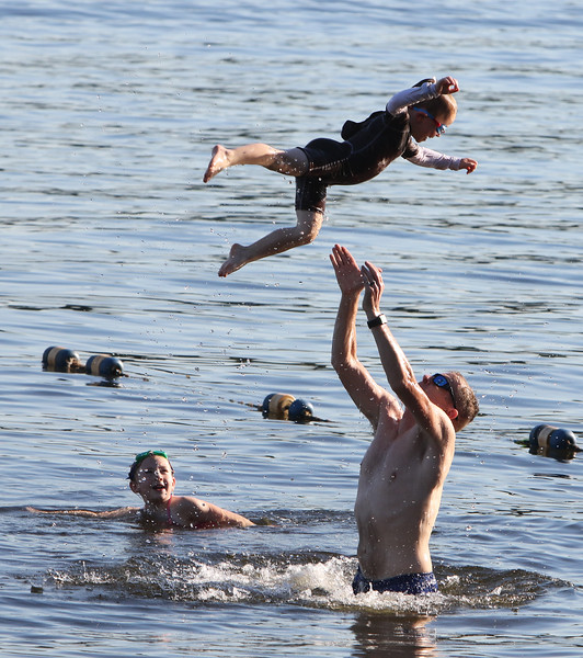 Features at Westford town beach at Forge Pond. Scott Brooks of Westford plays with his son Cameron, 5, and daughter Sadie, 9, left. (SUN/Julia Malakie)