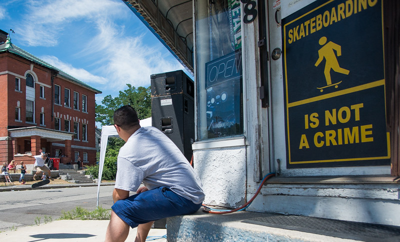 Dawson Stacy of Fitchburg sits on the steps of Acid Reign skate shop while watching a contestant in the Frankie Fortuna Skate Challenge held on Townsend St outside the shop. SENTINEL&ENTERPRISE/ Jim Marabello
