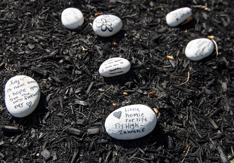 Rocks with hand-written messages are seen at the Frankie Fortuna bench in Leominster on Thursday afternoon. SENTINEL & ENTERPRISE / Ashley Green