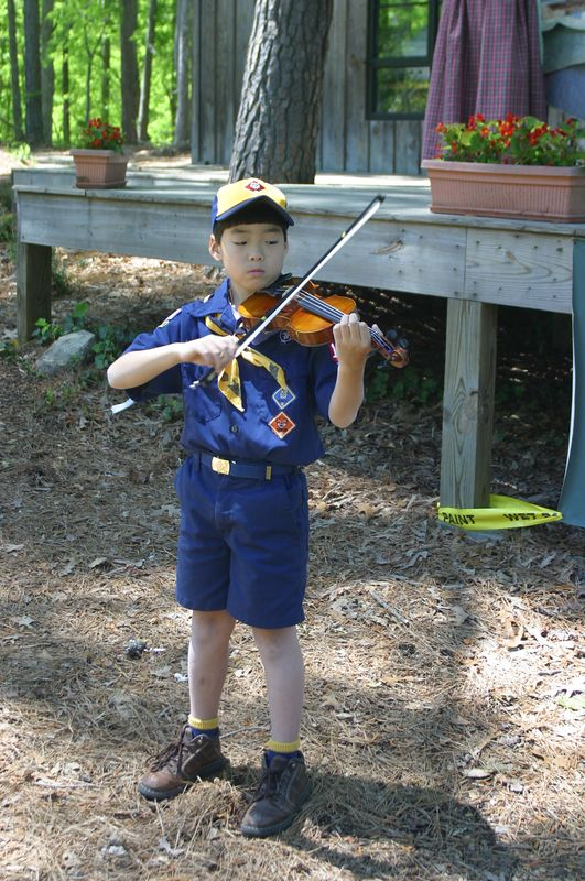 A cub scout practices his violin before playing for the crowd at the dedication of the Heritage Village at Autrey Mill Nature Preserve, Alpharetta, Ga., in May, 2005.