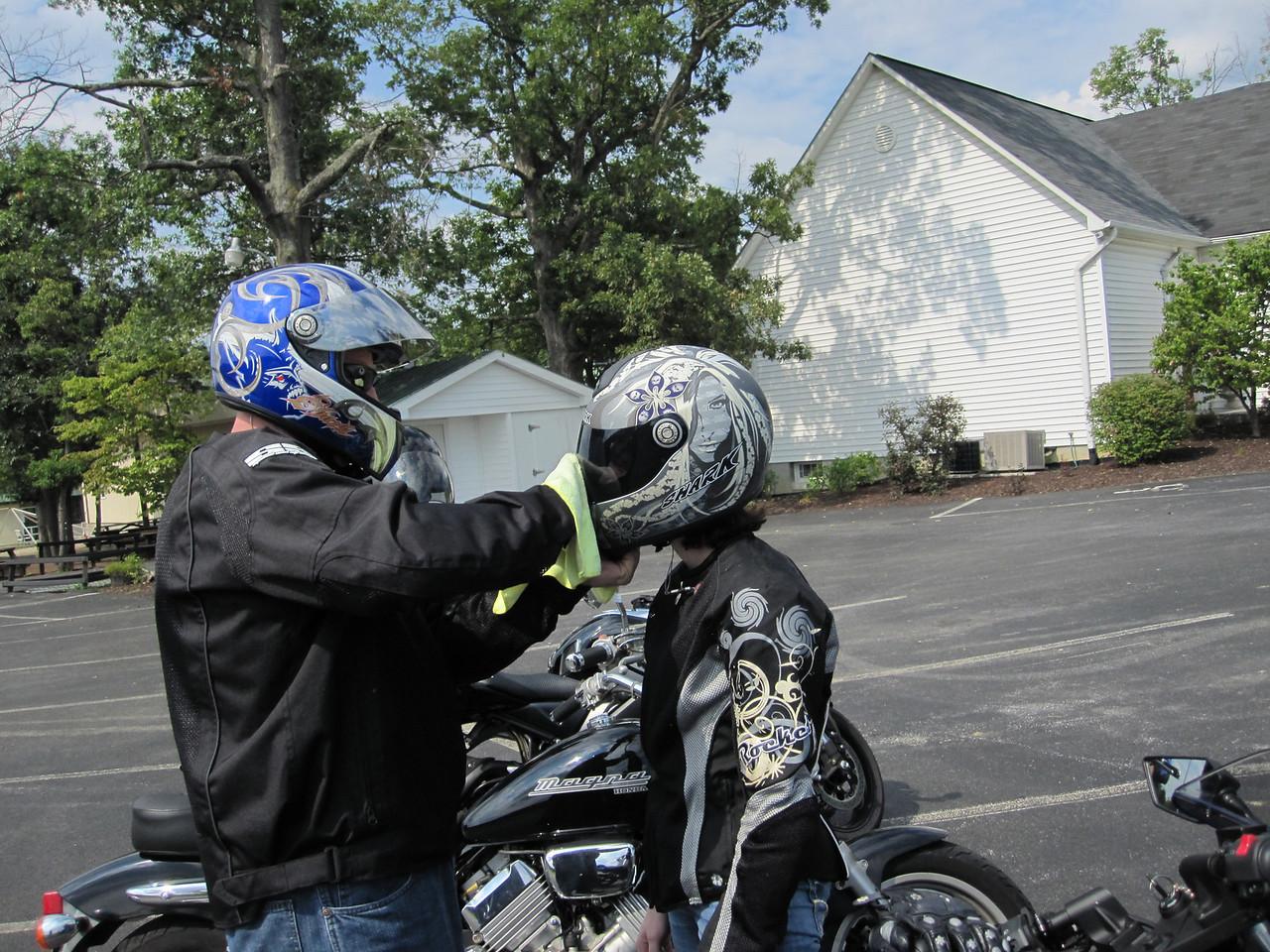 Greg cleaning Katie's helmet.