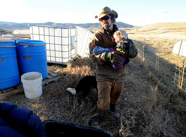 "Mike MacKinnon holds his daughter Poet, 2, while feeding the animals.<br /> Mike MacKinnon does the evening chores with his children on Frog Belly Farms in Boulder County. For more photos of the farm, go to  <a href=""http://www.dailycamera.com"">http://www.dailycamera.com</a><br /> Cliff Grassmick / December 16, 2010"