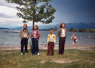 """Hazel snapped this Kodachrome of Janey, Evelyn, Alberta and a fourth girl that I do not recognize somewhere in Glacier National Park around 1949. All four girls have their hands in their pockets. I doubt this is an accident. However, it happened this is a great composition. The sky is dramatic, the busy kids in the water and on the beach add movement, and the four girls are all projecting """"sullen teenager."""" You can only fault the focus and that's probably due to Hazel's basic camera."""