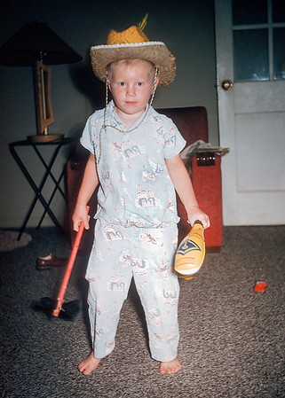 Here I am indulging myself with confused cultural appropriation. I am wearing a cowboy hat and swinging a tomahawk. In the 1950s I didn't wet my pajamas over alleged PC violations; I still don't. From one of Hazel's Kodachrome slides.