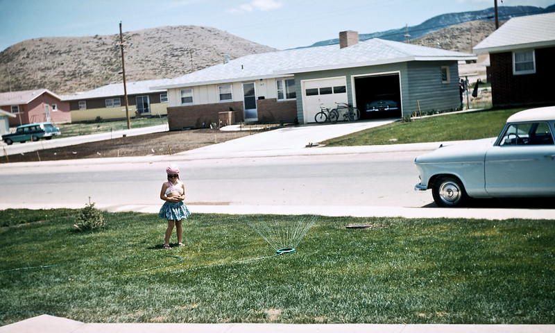 Aileen all dressed up for jumping in the lawn sprinkler. She's standing in the front yard of the first house our parents bought. We believe it was 168 Dahlia Street Casper Wyoming. In the larger sizes you can see the house number across the street is either 165 or 169. Hazel's old camera was not an optical gem but her slap dash shooting style produced some shots we are enjoying to this day.
