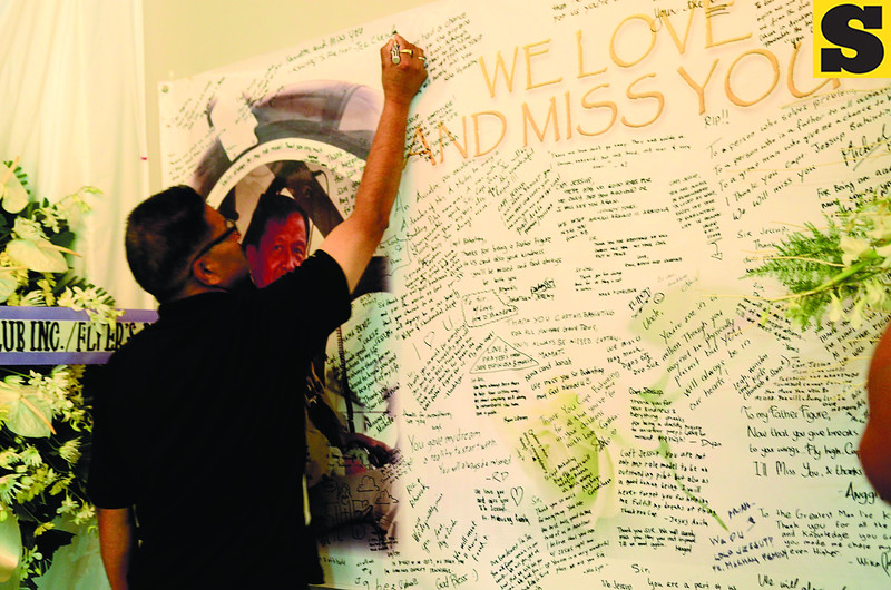 "CEBU.  Tek Bahadur Chand, whose son Kshitiz died in the plane crash last August 18, writes a message on a tarp at the wake for Capt. Jessup Bahinting. ""Namaste and miss you,"" he wrote.  (Amper Campaña)"