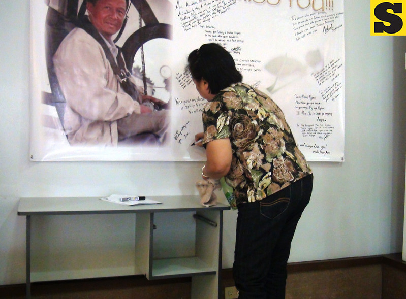 A friend of the Bahinting family writes her message for Captain Jessup Bahinting on the message wall prepared at the St. Peter's Funeral Homes in Cebu City. (Sunnex)