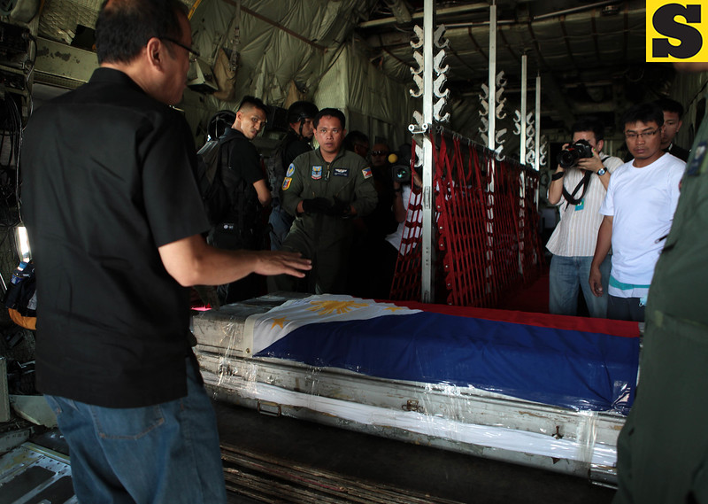 President Benigno Aquino III checks the safety of the casket containing the remains of Sec. Jesse Robredo on board C130 plane Tuesday, August 21, in Masbate airport.(Malacanang Photo Bureau)