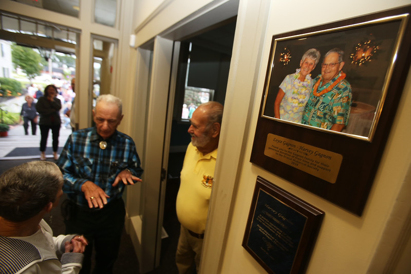 Dedication of Harvey J. Gagnon Harmony Hall. From left, Catherine Kope, a friend of Gagnon, Paul Bursey of Dracut, a neighbor, and David Paquin, chairman of the Dracut Historical Society, all of Dracut, talk in the lobby by a photo of Harvey and his wife Loyce Gagnon. (SUN/Julia Malakie)