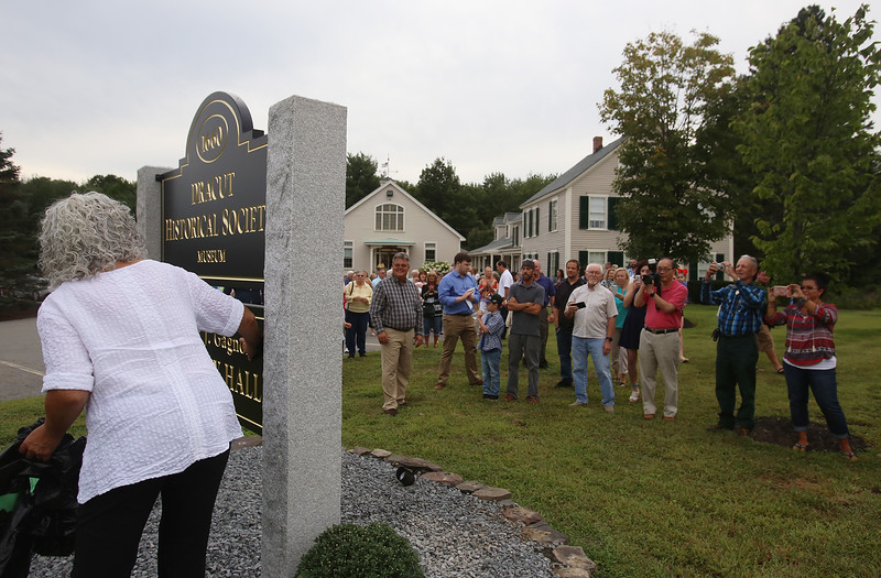 Dedication of Harvey J. Gagnon Harmony Hall. Michele Gagnon of Lyneborough, N.H., Harvey's oldest daughter, brushes off the new sign after its unveiling. (SUN/Julia Malakie)