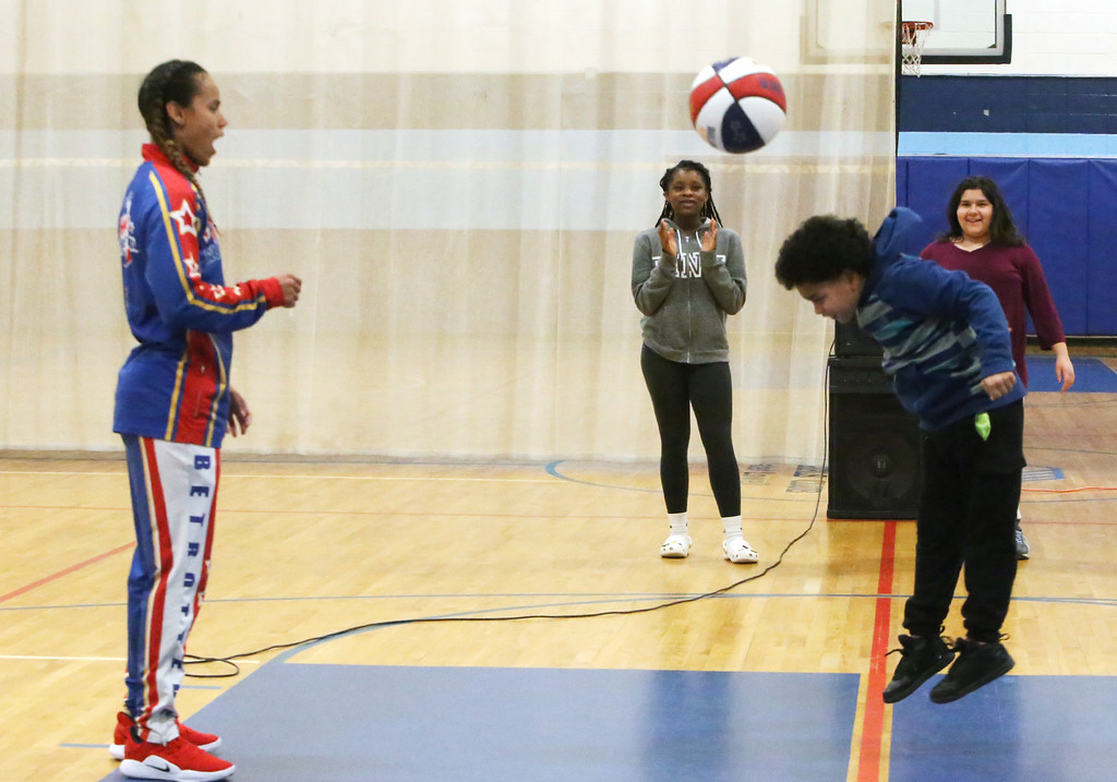 """. Harlem Globetrotter player Briana \""""Hoops\"""" Green visits the Boys & Girls Club of Greater Lowell to talk about the T.E.A.M. Up at School anti-bullying program, which stands for Talk, Empathize, Ask and Mobilize. Jeremiah Perez, 9, right, repeats a series of moves he\'d just been taught by Green, as Yvonne Welsh, 16, center, and Cailyn Champoux, 12, right rear, look on. The kids are all from Lowell. (SUN/Julia Malakie)"""