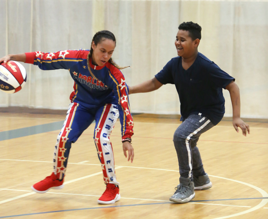 ". Harlem Globetrotter player Briana ""Hoops\"" Green visits the Boys & Girls Club of Greater Lowell to talk about the T.E.A.M. Up at School anti-bullying program, which stands for Talk, Empathize, Ask and Mobilize. Julius Richardson, 10, of Lowell, tries to steal the ball from Green.  (SUN/Julia Malakie)"