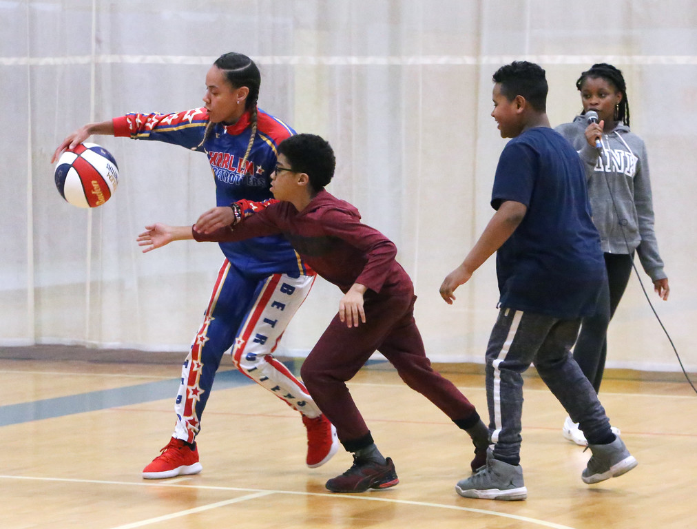 """. Harlem Globetrotter player Briana \""""Hoops\"""" Green visits the Boys & Girls Club of Greater Lowell to talk about the T.E.A.M. Up at School anti-bullying program, which stands for Talk, Empathize, Ask and Mobilize. Irwin Edwards, 12, front left, and Julius Richardson, 10, team up to try to steal the ball from Green, as Yvonne Welsh, 16, looks on. The kids are all from Lowell.  (SUN/Julia Malakie)"""