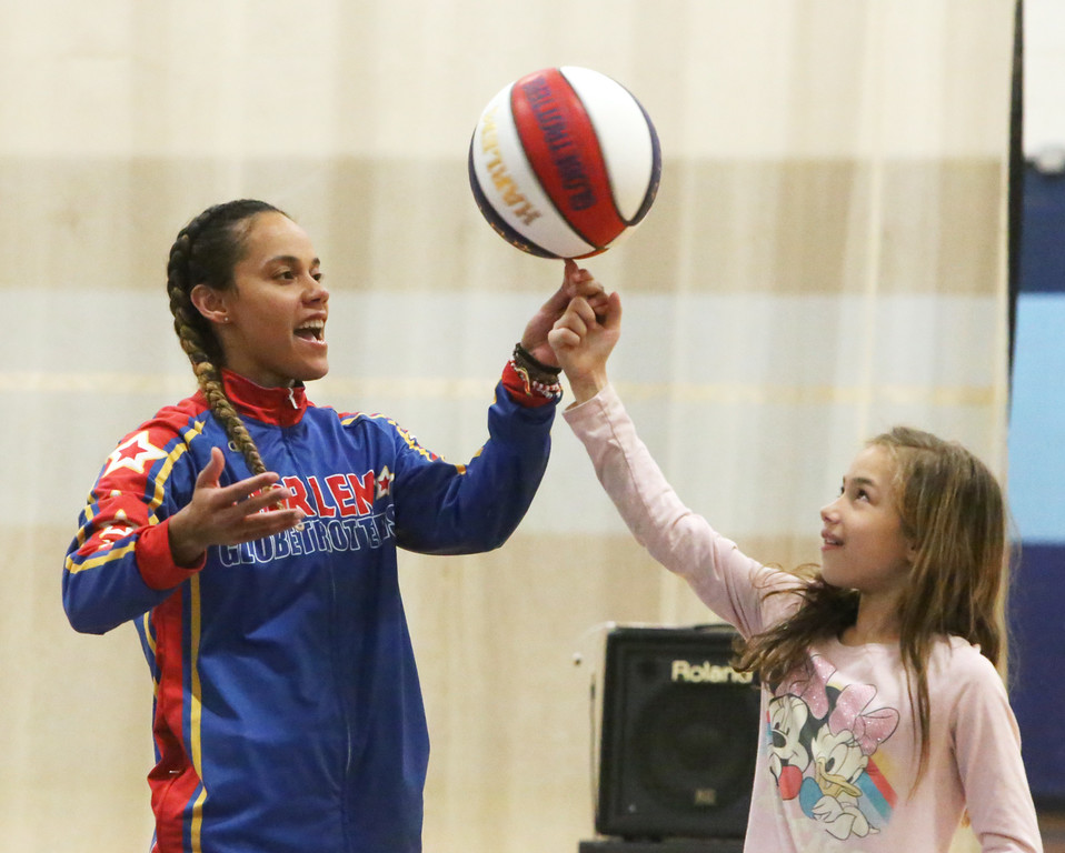 """. Harlem Globetrotter player Briana \""""Hoops\"""" Green transfers a spinning basketball to Joy Curran, 10, of Lowell, during a visit to the Boys & Girls Club of Greater Lowell to talk about the T.E.A.M. Up at School anti-bullying program, which stands for Talk, Empathize, Ask and Mobilize.  (SUN/Julia Malakie)"""