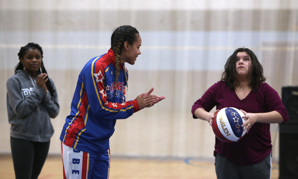 ". Harlem Globetrotter player Briana ""Hoops\"" Green visits the Boys & Girls Club of Greater Lowell to talk about the T.E.A.M. Up at School anti-bullying program, which stands for Talk, Empathize, Ask and Mobilize. Green encourages Cailyn Champoux, 12, of Lowell, to make a basket. At left is Yvonne Welsh, 16, of Lowell.  (SUN/Julia Malakie)"