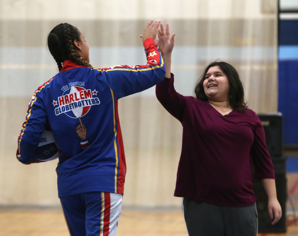 ". Harlem Globetrotter player Briana ""Hoops\"" Green visits the Boys & Girls Club of Greater Lowell to talk about the T.E.A.M. Up at School anti-bullying program, which stands for Talk, Empathize, Ask and Mobilize. Green high-fives Cailyn Champoux, 12, of Lowell after she made a basket after multiple tries. (SUN/Julia Malakie)"