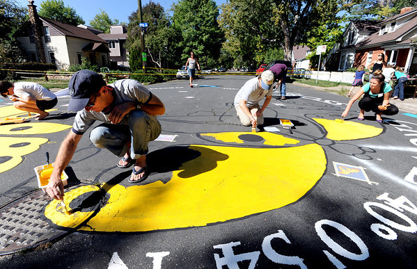 "Greg Mears,  bottom left, and Gina Martinez-Stranski, top right, were among about a dozen volunteers that worked on the Paint the Pavement project.<br /> Members of the Goss Grove Neighborhood Association spent much of Sunday painting the pavement at the intersection of 19th Street and Goss in Boulder.<br /> For more photos and a video, go to  <a href=""http://www.dailycamera.com"">http://www.dailycamera.com</a>.<br /> Cliff Grassmick / September 25, 2011"
