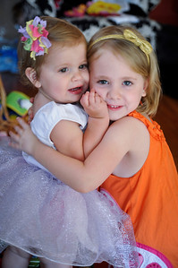 Matilda in her party dress getting a big hug from her sister.