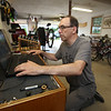 Doug Browne of Groton, who repairs used bikes and donates them to the Boys & Girls Club of Greater Lowell and the Nashua Soup Kitchen, checks his records of bikes he's done. (SUN/Julia Malakie)