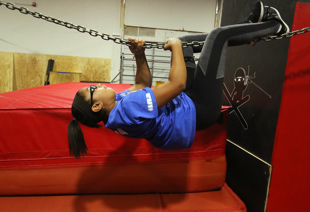 . Analise Grady, 14, of Billerica, who participated in American Ninja Warrior Jr., works out on the chain at Gymja Warrior in Woburn. (SUN/Julia Malakie)