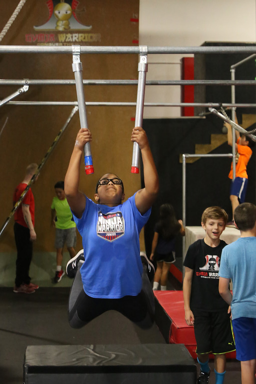 . Analise Grady, 14, of Billerica, who participated in American Ninja Warrior Jr., works out on the nunchucks at Gymja Warrior in Woburn. (SUN/Julia Malakie)