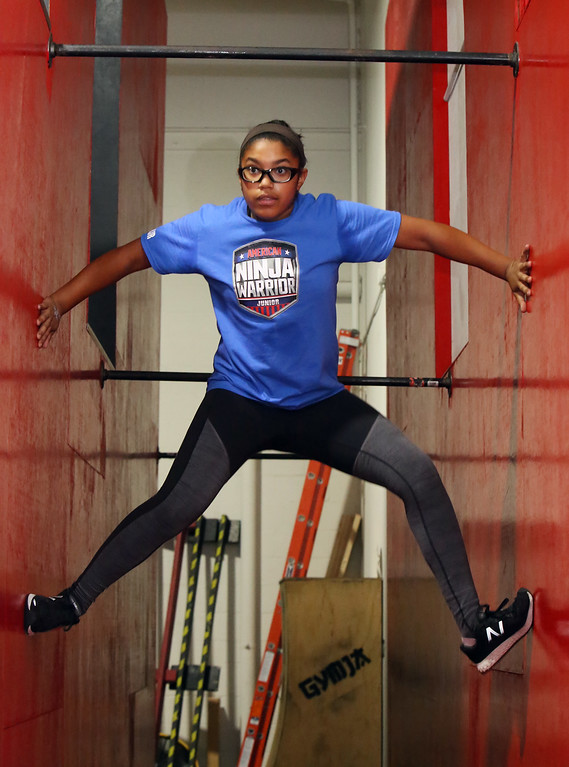 ". Analise Grady, 14, of Billerica, who participated in American Ninja Warrior Jr., does the ""spider climb\"" at Gymja Warrior in Woburn. (SUN/Julia Malakie)"