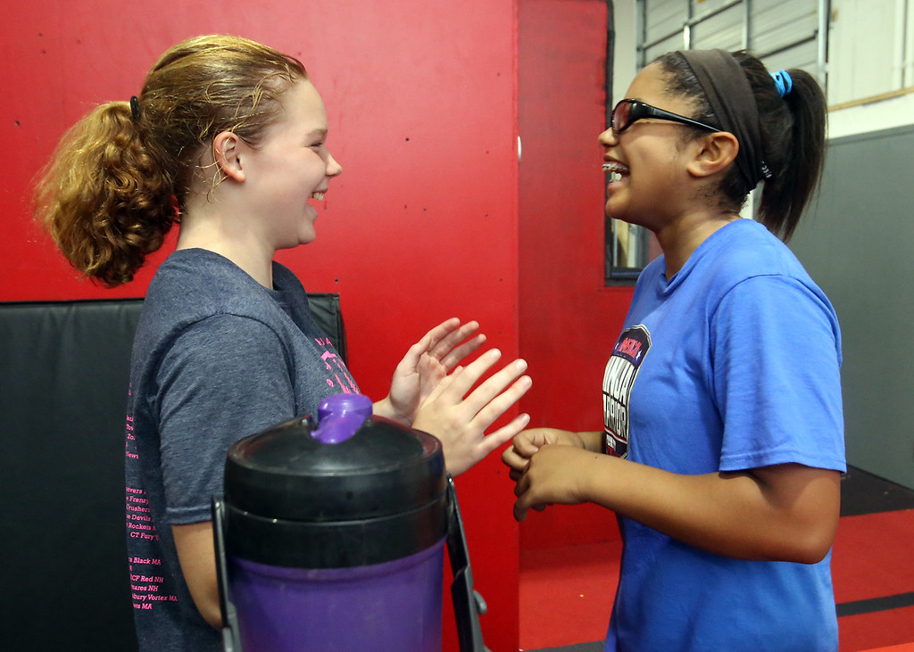 . Analise Grady, 14, of Billerica, right, who participated in American Ninja Warrior Jr., and her friend Naomi Boldebuck, 13, also of Billerica, take a break during class at Gymja Warrior in Woburn. (SUN/Julia Malakie)