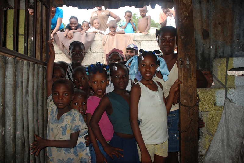 Village children watching throught the doorway.