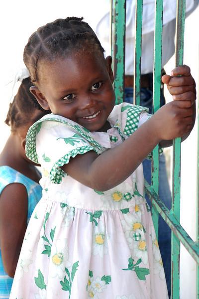 Little girl swinging on the church door.