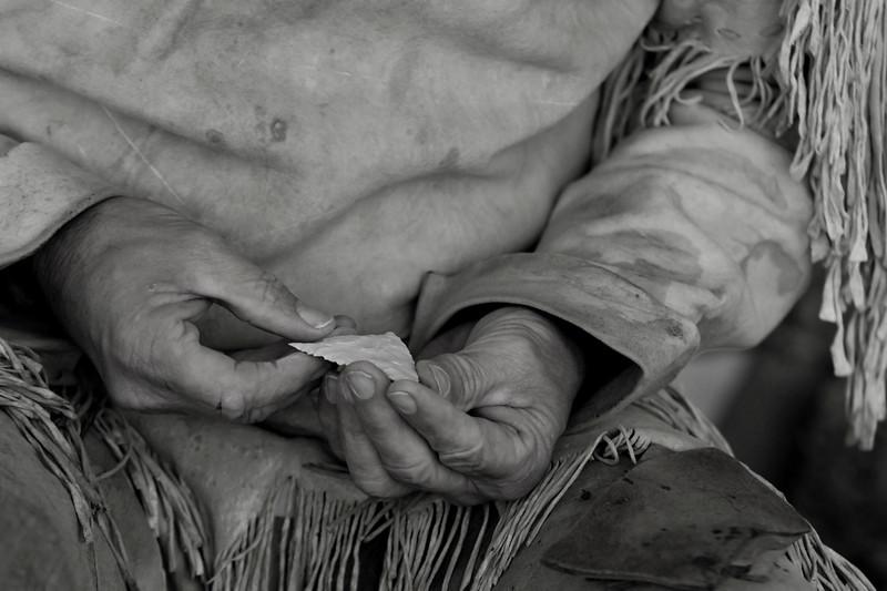 A flint knapper inspects his work