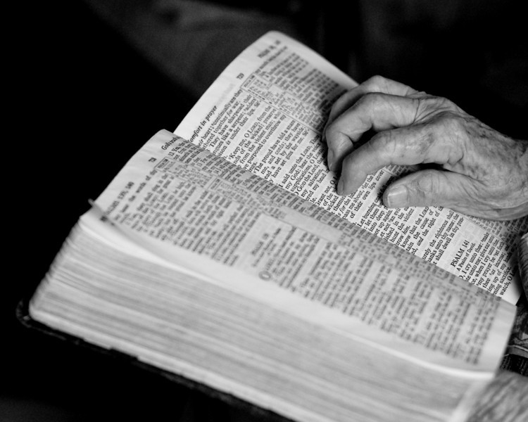 Grandmothers hand on the Bible