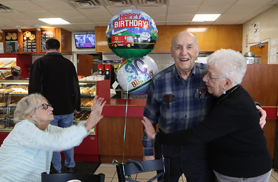 Friends of retired Lowell arson investigator Harold Waterhouse hold a birthday celebration at Top Donut for his 90th birthday. From left, Brenda McMeniman of Lowell, Harold Waterhouse and his wife Marion Waterhouse.(SUN/Julia Malakie)