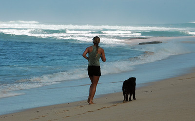 Female jogger with her dog running along a beach on the North Shore North Shore of O'ahu, Hawai'i