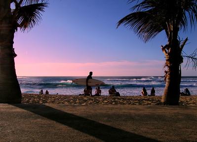 Surfer carrying his board, walking along Sunset Beach at sunset North Shore of O'ahu, Hawai'i