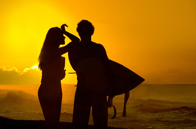 Silhouette of a surfer and his girlfriend at Sunset  Sunset Beach, North Shore of O'ahu, Hawai'i