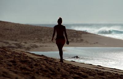 Pretty female in a bikini walking on the beach  North Shore of O'ahu, Hawai'i