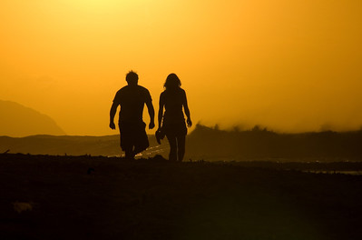 Couple walking along the beach at sunset  North Shore of O'ahu, Hawai'i