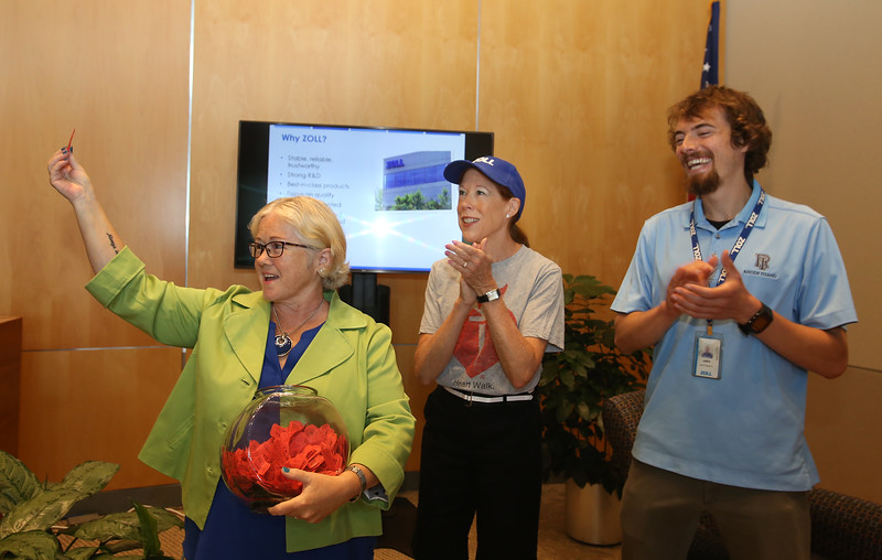 Susan Schumacher of Billerica, center, a volunteer and part-time administrator with the Zoll Foundation, at raffle drawing to benefit the American Heart Association Heart Walk, as global travel manager Nan Lindstrom of Westford pulls the winning ticket for $500 of Lyft rides. At right is software test engineer John Paquet of Woburn. (SUN/Julia Malakie)