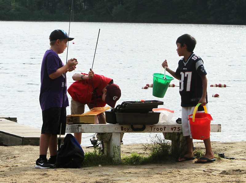 Features at Heart Pond in Chelmsford. Riley Stout, left, and Ethan McCafferty, center,  both 11 and from Chelmsford, join Ryan Heng, 11, of Chelmsford, who was already fishing at Heart Pond. They were expecting to most likely catch sunfish.  (SUN/Julia Malakie)