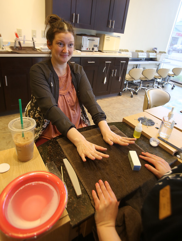 . Donna Rains of Somerville, who is being treated for a recurrence of breast cancer, extends her newly manicured nails during a surprise makeover at Pyara Spa and Salon in Burlington, the first salon in Massachusetts participating in the Hello Gorgeous program. (SUN/Julia Malakie)