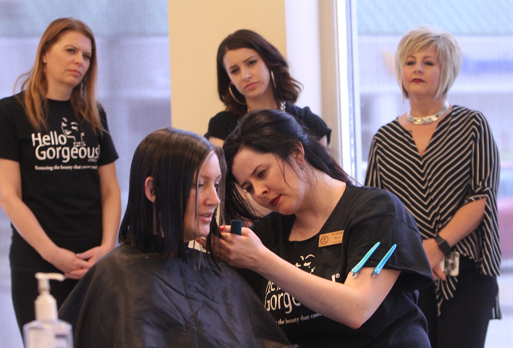 . Donna Rains of Somerville, who is being treated for a recurrence of breast cancer, is treated to a surprise makeover at Pyara Spa and Salon in Burlington, the first salon in Massachusetts participating in the Hello Gorgeous program. Master stylist Taylor Macdonald cuts Rains\' hair. Watching, from left: Pyara owner Christine Perkins of Lexington, stylist apprentice Cat Moore of Arlington, and Ann Hudson from South Bend, Indiana, affiliate salon coordinator with Hello Gorgeous, which provides training and then supervises the first session each salon does. (SUN/Julia Malakie)