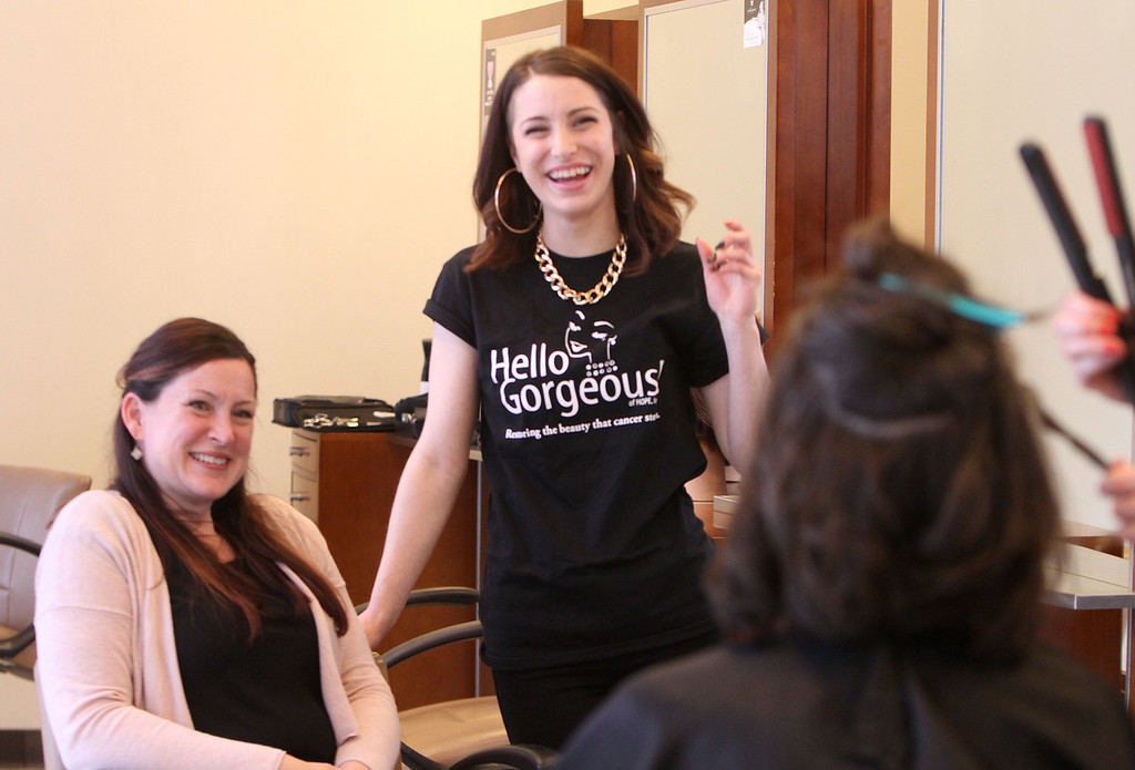 . Donna Rains of Somerville, who is being treated for a recurrence of breast cancer, is treated to a surprise makeover at Pyara Spa and Salon in Burlington, the first salon in Massachusetts participating in the Hello Gorgeous program. Rains\' sister, Ellen Savino of Bridgewater, left, and stylist apprentice Cat Moore of Arlington watch the haircut. (SUN/Julia Malakie)